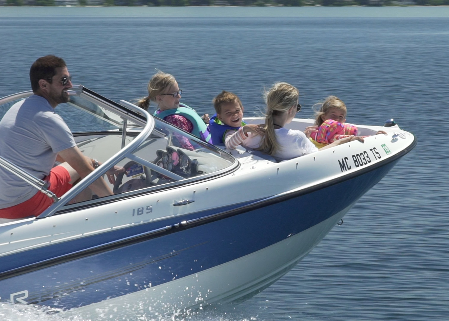 Family of five having fun in a ski boat