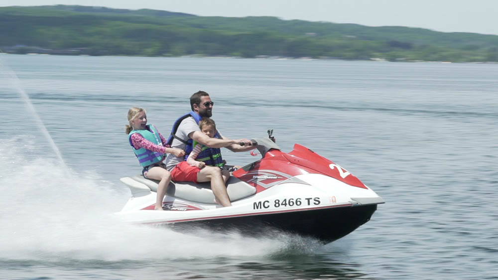 Side view of a father and two children enjoying a ride on a red jet ski