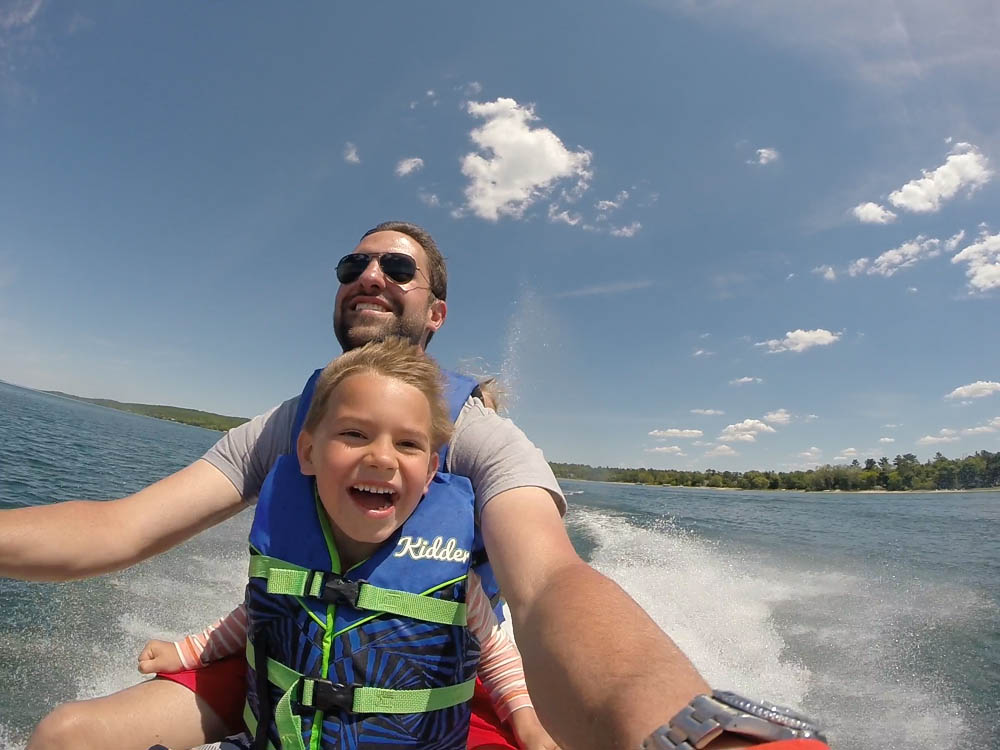 A happy boy and his father enjoying a ride on a jet ski