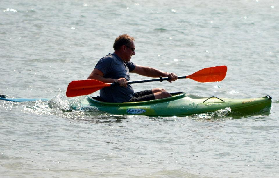 Man on the water in a green kayak.