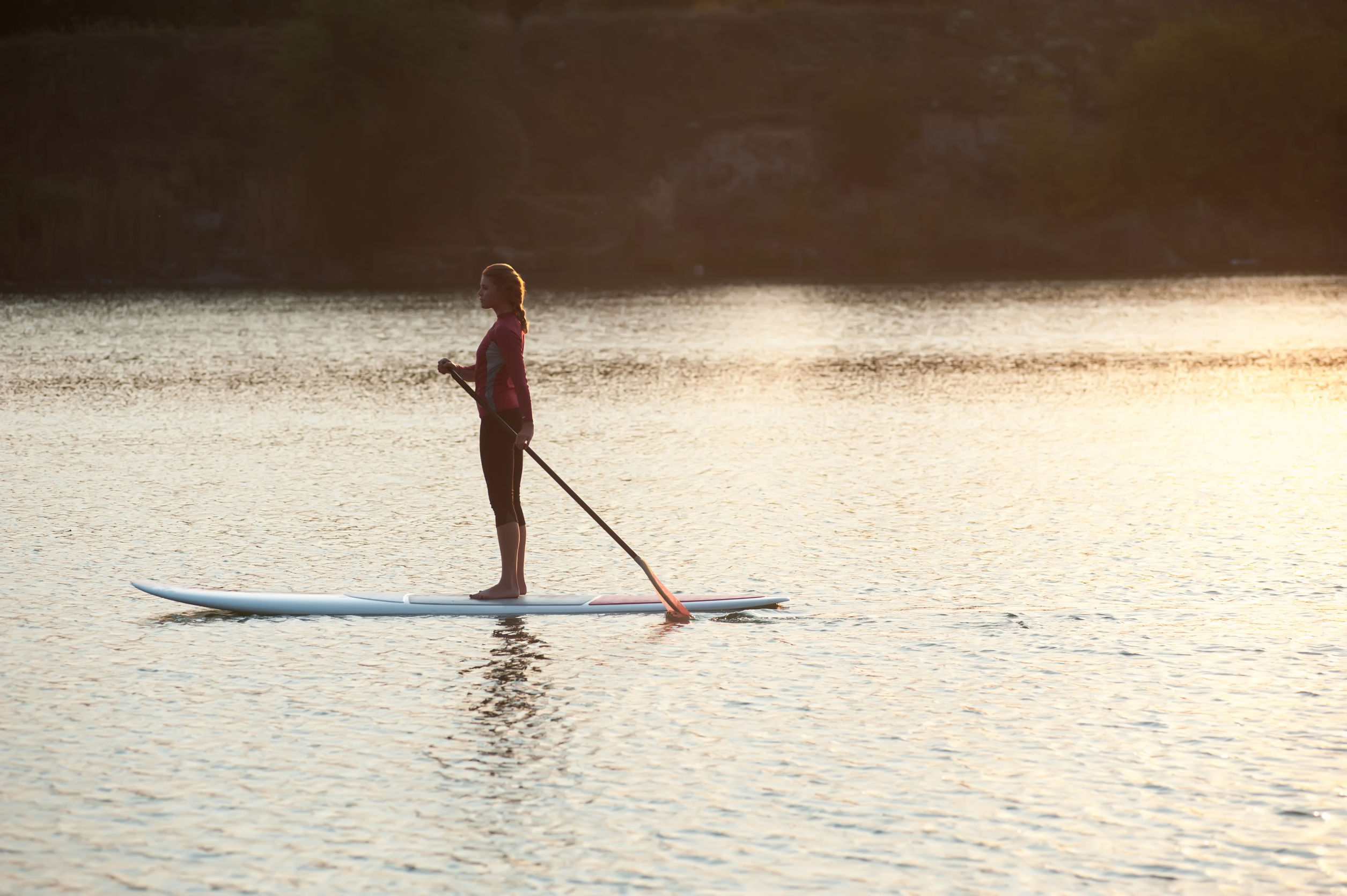 Young lady standing on a Stand up Paddle Board in the water