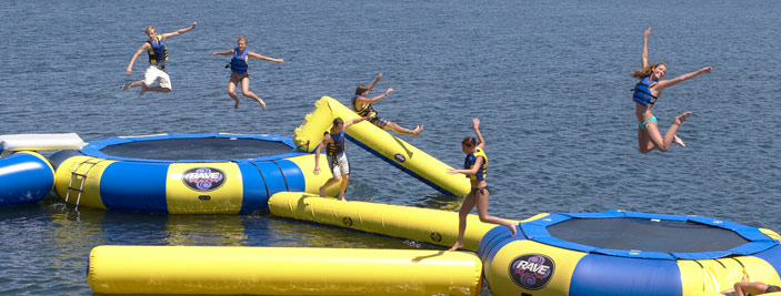Young people jumping on trampolines in water