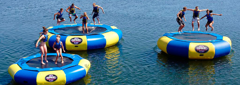 Three Rave Trampolines in the water with young people jumping on them