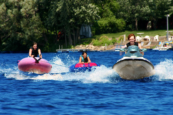 Young people tubing with a jet ski